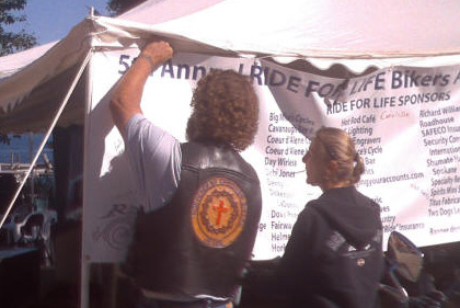 Volunteers put up a Ride for Life banner at the event.