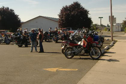 Motorcycles and people in parking lot before event.