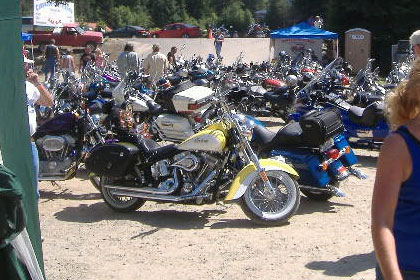 Parking lot filled with motorcycles and a few people.