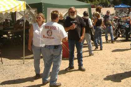Group of people talking outside of a tent surrounded by motorcycles.