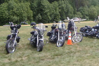 Line of motorcycles parked in grass with small airplanes parked in background.