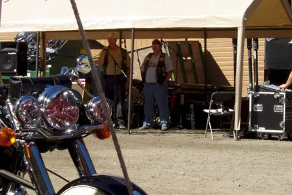Motorcycle parked in foreground. Men stand in and around tent in background.