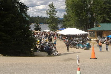 Far away shot of parking lot filled with motorcycles and tents.