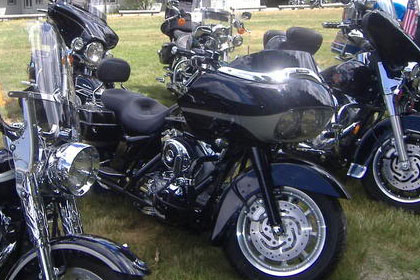 Close up shot of several motorcycles in parking area.
