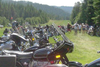 Long lines of motorcycles stretch into the distance with small planes in background.
