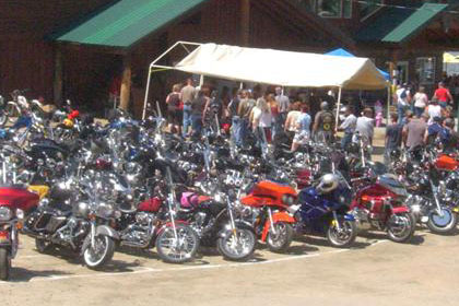 A lot of motorcycles and people in parking lot.