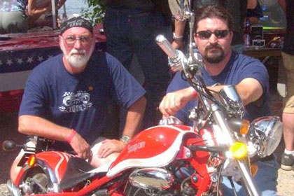 Two men pose with motorcycle.