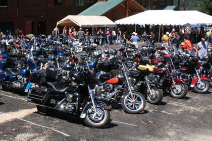 Lots of motorcycles fill parking lot outside of event venue.