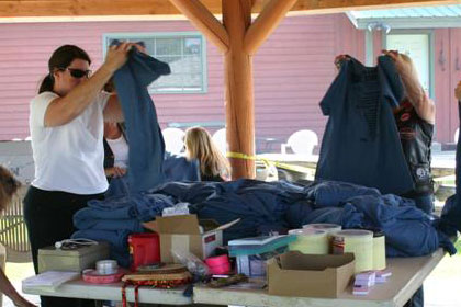 Women folding stacks of Ride for Life t-shirts onto tables.