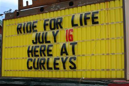 Yellow sign advertises event outside of Curley's.