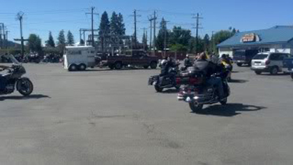 Some riders on their motorcycles in the parking lot.