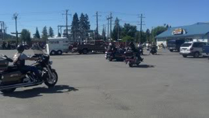 People on their motorcycles in the parking lot.