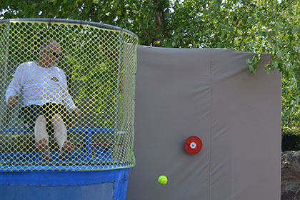 Children throwing balls at the dunk tank.