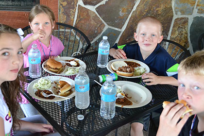 Children eating barbecue at a table outside.