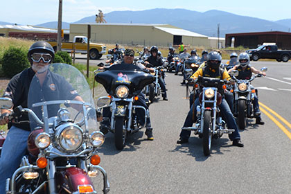 Riders line up on their motorcycles.
