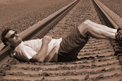Man relaxing on railroad tracks.
