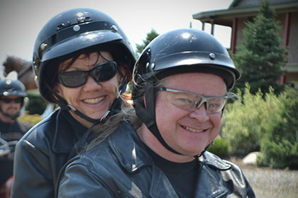 Two riders on a motorcycle smile for the camera.
