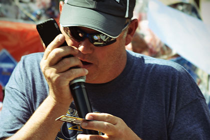 Man wearing a hat and sunglasses speaks on the microphone.