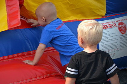 Children climbing into the bouncy castle.
