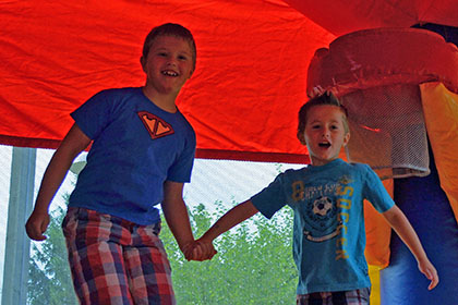 Two boys jumping in the bouncy castle.