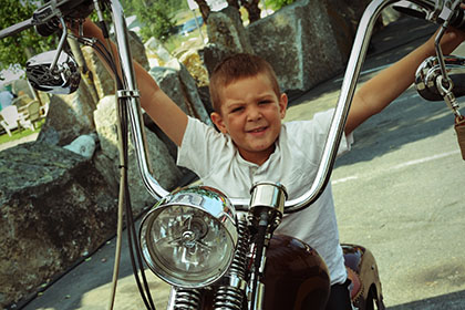 Child sitting on motorcycle.