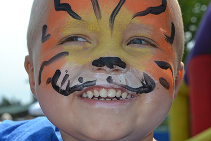 Child with their face painted like a tiger.