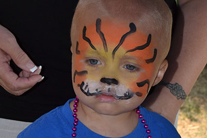 Child with their face painted.
