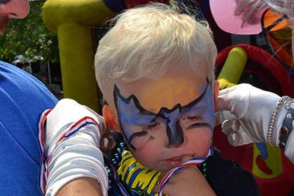 Child with their face painted as Batman.