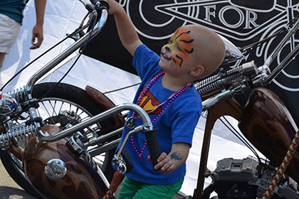 A painted face child on the display motorcycle.