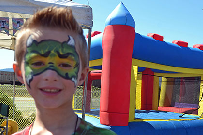Child with painted face stands in front of a bouncy castle.