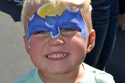 Young child with a painted face smiles for the camera.
