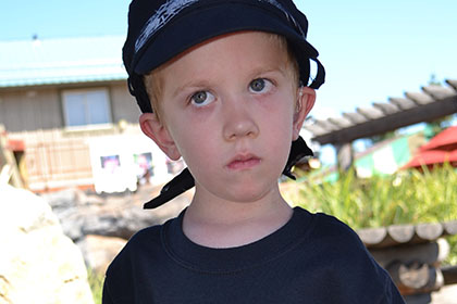 Child wearing a hat at the event.