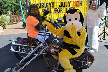 Skitch from Spokane Community College, a bee, and another person in costume, pose on motorcycles for a photograph.