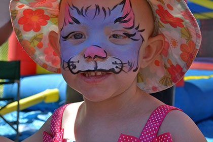 A child with a painted face and wearing a hat.