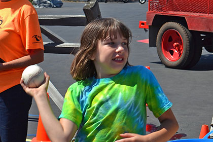 Child getting ready to throw a ball at the dunk tank.