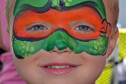 Child with their face painted like a Ninja Turtle.