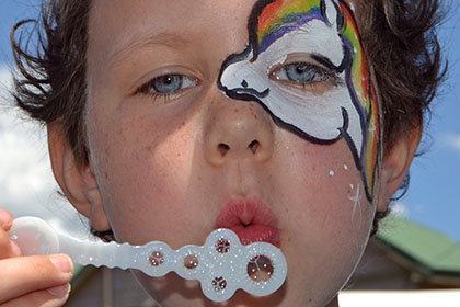 Child with a painted face blowing bubbles.