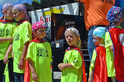 Group of children wearing Ride for Life shirts, capes, and bandanas.