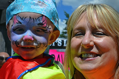 Woman holding a child with a painted face.
