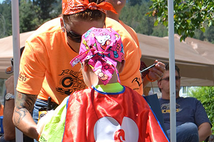Ride for Life volunteer helping a child wearing a red cape and pink bandana.