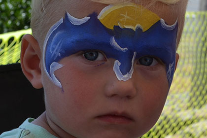 Child with a Batman painted face.