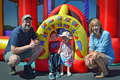A man, woman, and two children pose for a photograph in front of a bouncy castle.