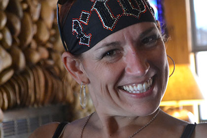 A woman wearing a bandana smiles for the camera.
