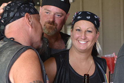 A woman next to a couple guys smiles at the camera.