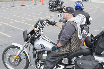 Riders wait on their motorcycles in the parking lot.