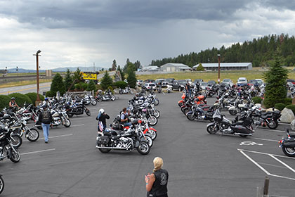 Motorcycles and vehicles in the parking lot at the event.