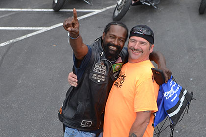 Bearded man and Ride for Life volunteer smile for the camera.