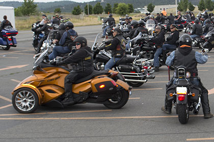 Group of riders gather in a parking lot.