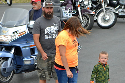 A bearded man, Ride for Life volunteer, and child walk in the parking lot.