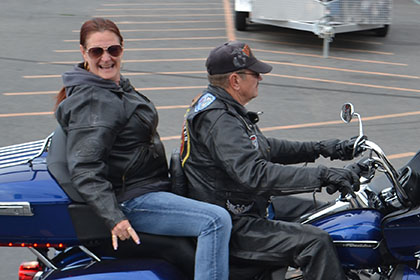 Man and woman on a blue motorcycle.